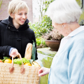 Woman giving shopping basket of helathy food to older woman