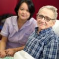 Man in pyjamas with a nurse, both smiling