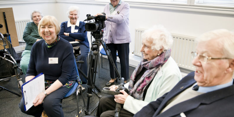 picture of older people smiling holding a camera and recording equipment